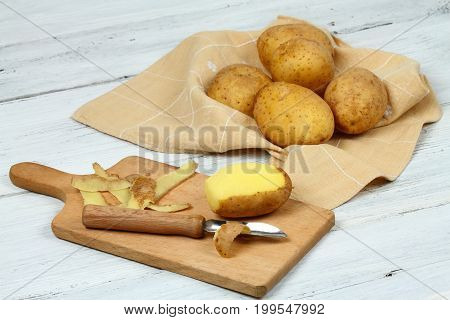 Peeling raw potatoes with old peeler on the white table. Some potato peels on the chopping board