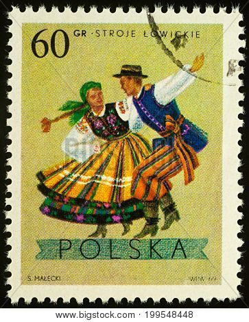 Moscow Russia - August 11 2017: A stamp printed in Poland shows dancing couple in traditional costumes from Lowicz Lodz series