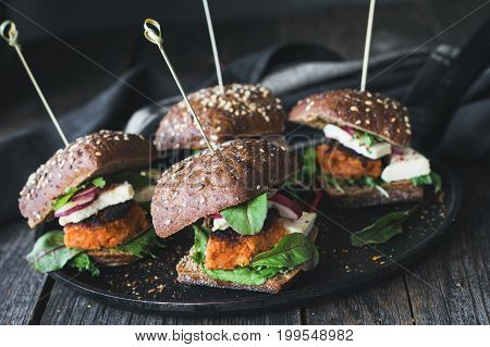 Vegetarian tofu carrot burger sliders served on iron skillet. Closeup view, toned image
