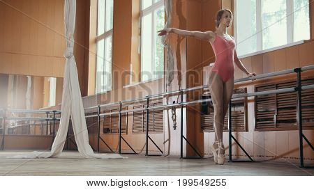 Model girl in pink dress and pointe shoes ballerina practicing in the Studio, wide angle view
