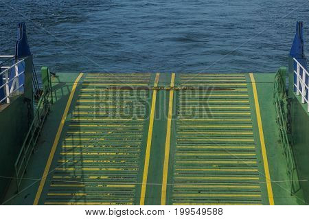 Ferry boat yellow green colour ramp for loading vehicles.As the ramp is moving down & the ferry is approaching the dock.