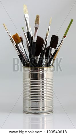 Sevaral different paintbrushes in a tin bucket