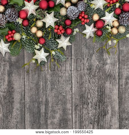 Christmas background border with bauble decorations, holly, ivy, mistletoe, fir and pine cones on old rustic wood background.