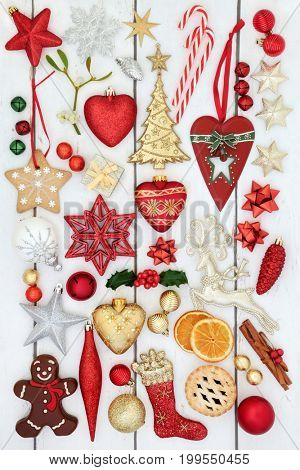 Christmas symbols with bauble decorations, holly, mistletoe, mince pie, gingerbread biscuit  and chocolate candy on rustic white wood background.