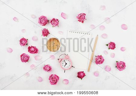 Morning coffee cup for breakfast empty notebook petals alarm clock and pink rose flowers on white stone table top view in flat lay style. Woman working desk.
