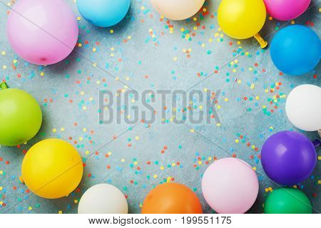 Colorful balloons and confetti on turquoise table top view. Birthday holiday or party background. Flat lay style. Empty space for text. Festive greeting card.