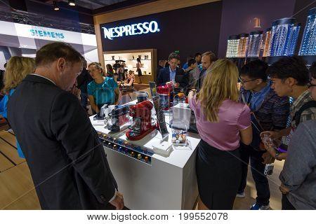 BERLIN - SEPTEMBER 04 2015: Visitors taste the coffee from the Nespresso. International radio exhibition Berlin (IFA2015).