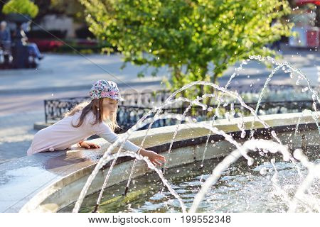 little preschooler girl playing with a city fountain