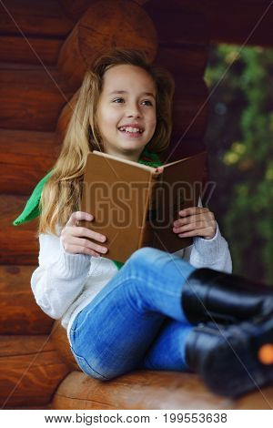 dreaming beautiful girl reading a book outdoors