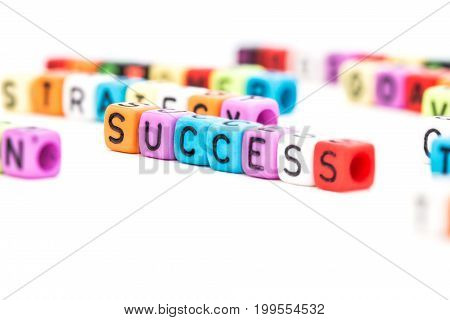 colorful SUCCESS english alphabet cube on white background selective focus