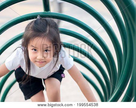 Happy kid asian baby child playing on playground climb the playground equipment circle shape white T shirt