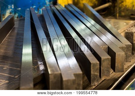 Straight row of metal bars after grinding. Metalworking.