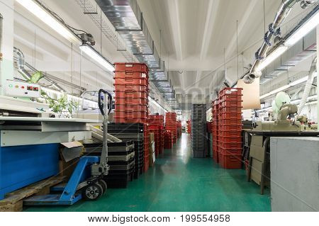 Stacks of red and gray plastic boxes, shoe factory.
