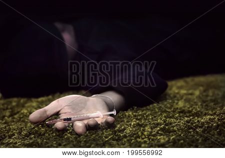 Hand Of Man Lying On The Floor With A Syringe