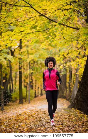 Fitness woman running in tracksuit, full-length shot.