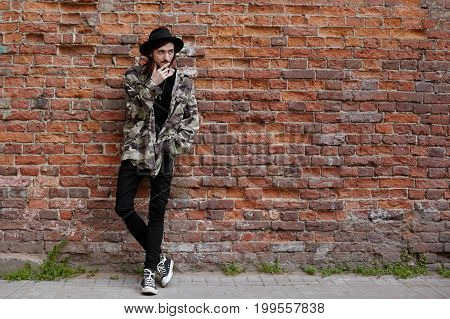 Thoughtful bearded young male hipster wearing trendy outfit posing outdoors standing at red brick wall background with copy space area for your information advertisement or promotional content