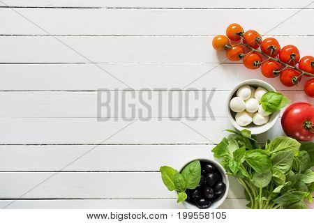 Fresh food ingredients for italian cuisine. Bunch of green basil, black olives, mozzarella cheese and tomatoes on white wooden background. Top view with copy space