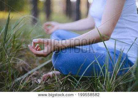 Woman Practices Yoga And Meditates In The Lotus Position On The Nature. Girl Meditate At The Forest.