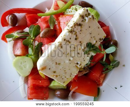 View on a traditional Greek Salad with Sheep Cheese, fresh Spices, cucumbers, Olives and red Tomatoes. Close-up of a healthy Greek Salad on a white Plate.