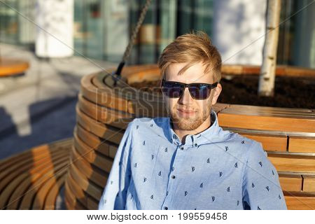 Headshot of stylish Caucasian guy with stubble wearing trendy mirrored lens shades and shirt relaxing outdoors sitting on round wooden bench alone in city park looking and smiling at camera