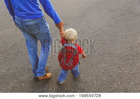 father walking little daughter to school or daycare