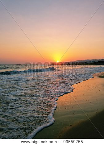 View on a beautiful warm Sunrise at the Beach. Enjoy the Sunrise of a new Day. The Light of a Sunrise is shining on the peaceful Waves of a Beach.