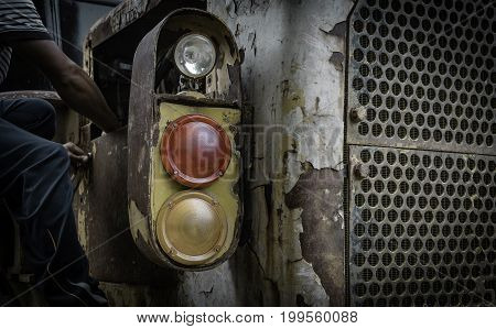 Man repairing headlight of old tractor in vintage and retro tone.