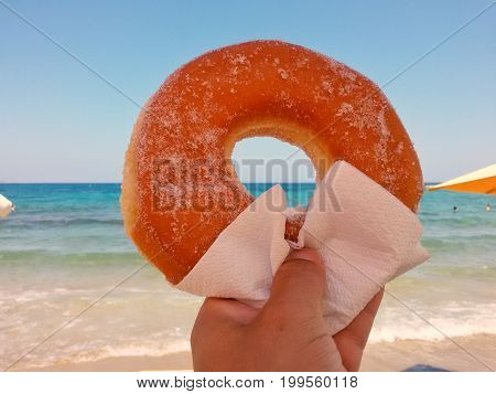 Close-up of a Donut in a human Hand in front of a Beach.View on a tasty Donut with Sugar. A Men holds a Donut.