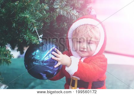 Boy in santa claus costume holding blue Christmas ball on tree on sunny background. Xmas and new year decoration and ornament. Winter holiday celebration concept. Child and happy childhood