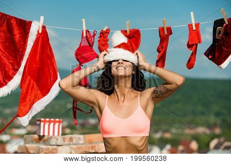 Xmas red costume on rope with pin. Laundry and dry cleaning. Christmas woman with happy face outdoor. New year girl on sunny blue sky. Santa claus girl hanging clothes for drying.