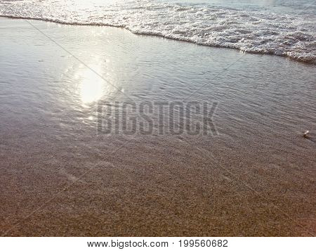 View on a Beach covered by Crystal clear Water. Close-up of a Beach in Summer. Peaceful Ocean waves at Beach. Sunlight is shining on a Beach