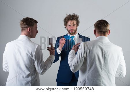 Businessmen exchanging cards on grey background. Group of people facing each other. Men wearing white jackets back view. Information and cooperation. Business ethics concept.