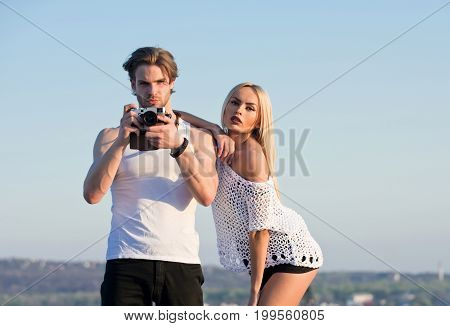 Guy with photo camera on athletic chest. Man with muscular body with girlfriend. Girl with photographer outdoor. Couple in love and romance. Beauty and art fashion.