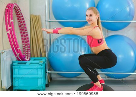 Beautiful young woman doing fitness in the gym. Girl uses fitball exercise, expander, hemisphere.