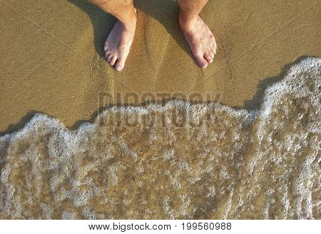 View on Feet in the Water. Close-up of Feet on sandy bottom in front of peaceful Ocean Waves.