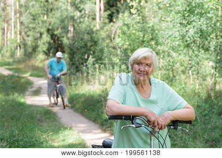 happy senior couple riding bikes in summer nature