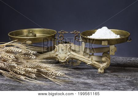 Vintage kitchen scales with scoop of flour are standing on the old wooden desk. The bundle of corn lies in the foreground.