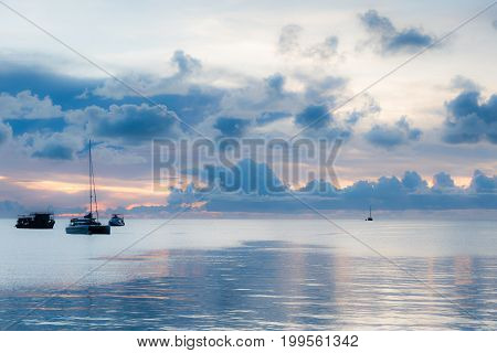 Soft Focus Of Boats In Sea Amidst Dark Clouds At Sunset.