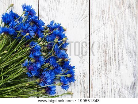 blue cornflowers on a old white wooden table