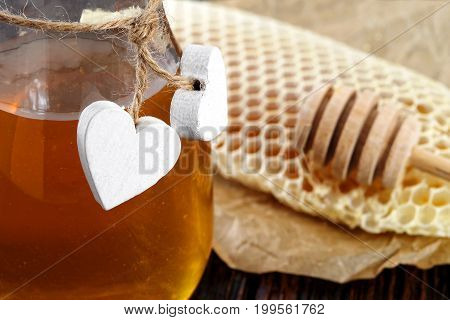 Jars of honey bee honeycomb and bee pollen on wooden table with wax honeycomb