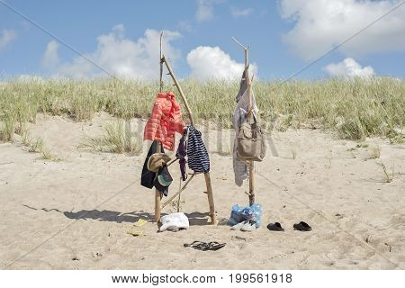 clothes hanging on the wooden poles at the beach, windy, cold summer