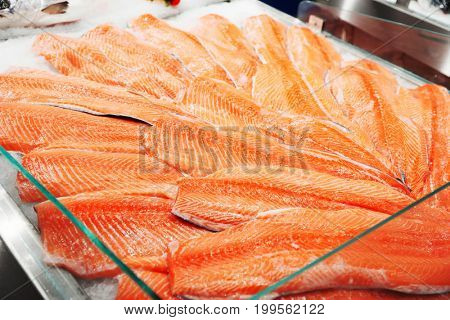 Salmon fillets on iced market display in food store, toned image