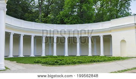In a public park on a summer day a beautiful colonnade surrounded by green trees