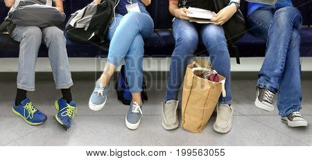 Four young people sitting in a subway train