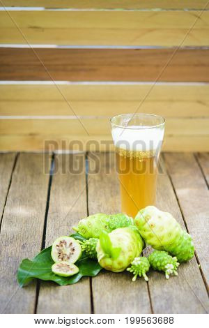 Noni fruit and noni juice and blossom on old wooden table.Vertical.