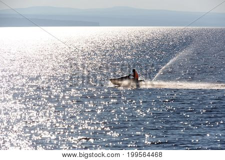 man on the aquabike in a backlight with glare on the water