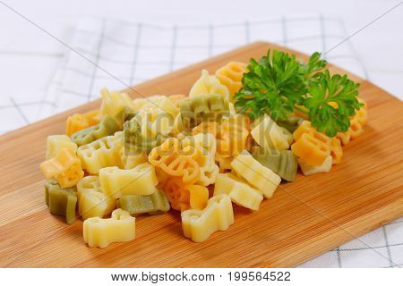 pile of cooked colored pasta on wooden cutting board - close up