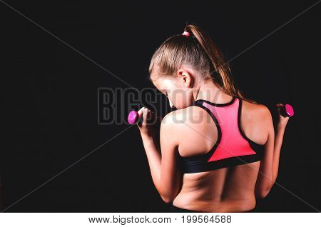 Young fitness girl with dumbbells on black background. Sport or healthy lifestyle concept
