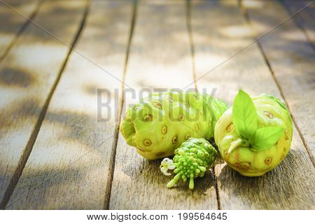 Noni fruit and blossom on old wooden table. Close up