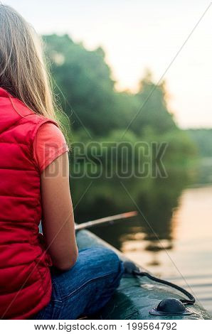 Girl With A Fishing Rod In Hand, Sits In A Boat And Catches Fish